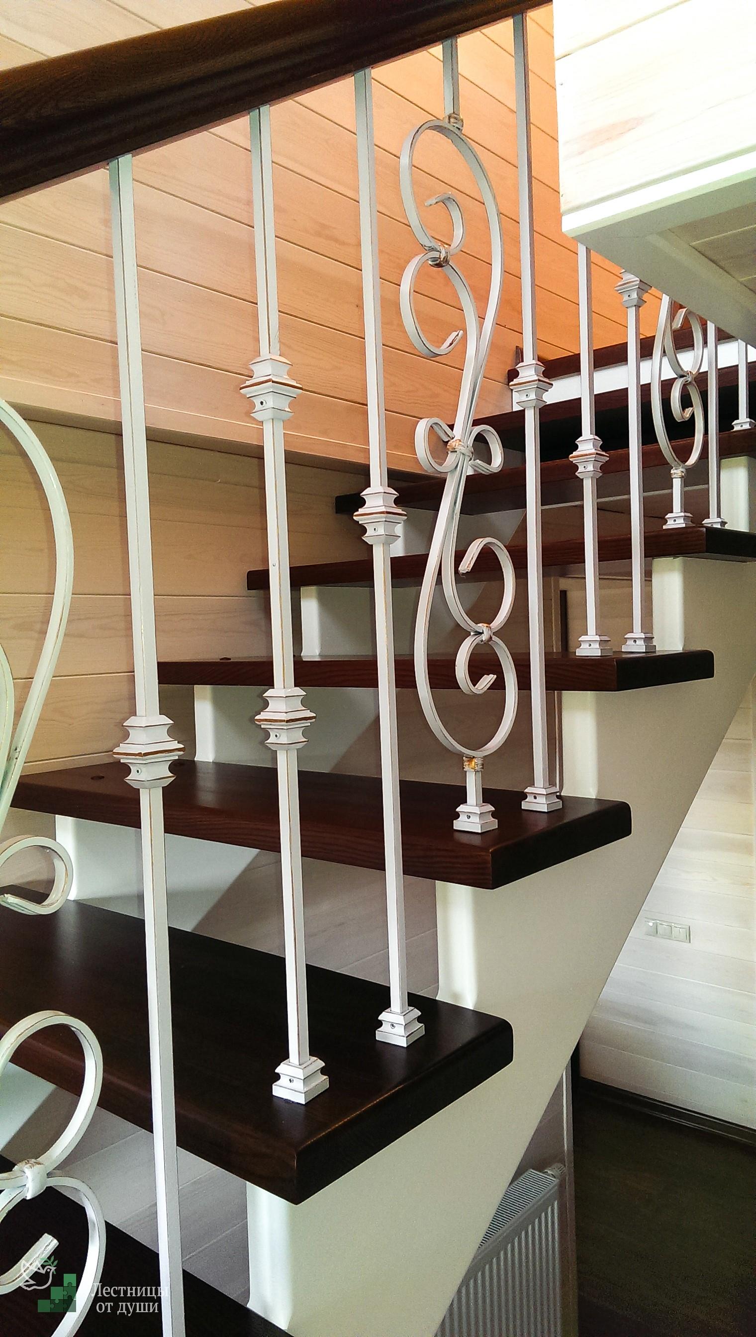 Двухцветная лестница с кованым ограждением