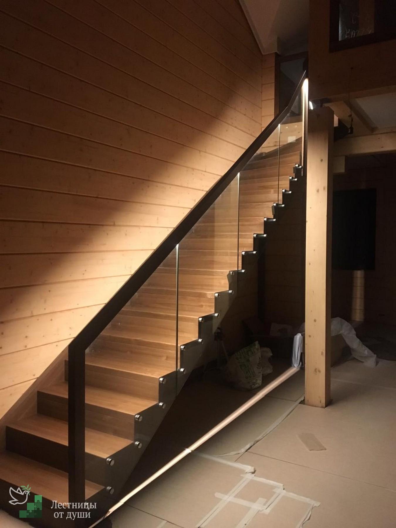 Деревянная лестница в доме со стеклянными ограждениями